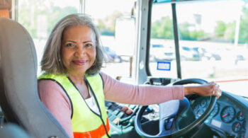 A senior female bus driver turns to look at the camera from the driver's seat of her school bus. She has one hand on the steering wheel.